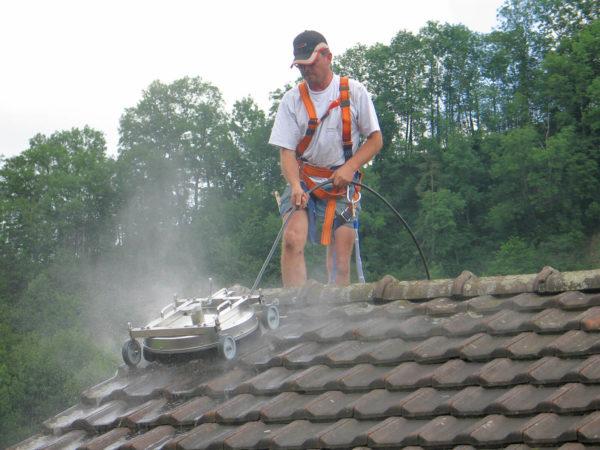 Mies pesee tiilikattoa mosmatic katon pesulaitteella