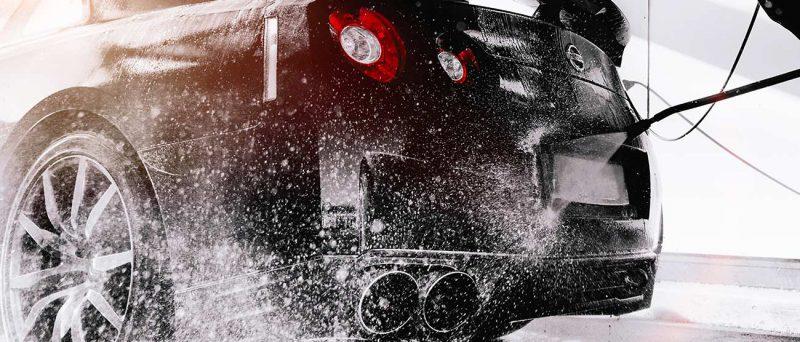 Mustaa autoa pestään painepesurilla