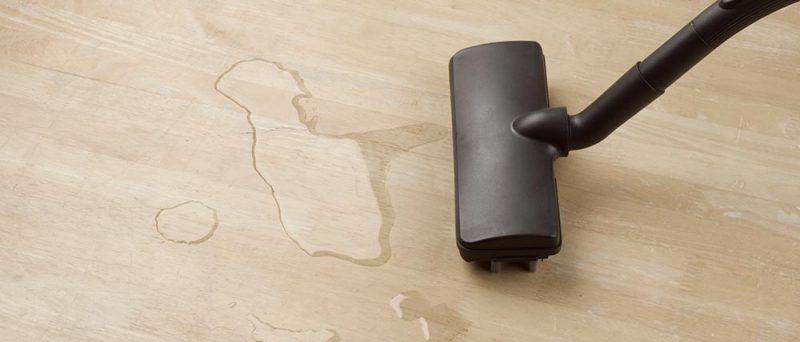 Imuri puhdistaa vesiroiskeen parkettilattialta